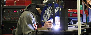 Student welding in Newton