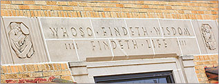 Building engraving that reads 'Whoso Findeth Wisdom Findeth Life'