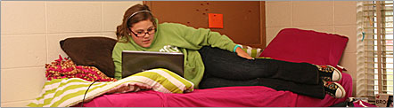 A female student relaxes in their dorm room